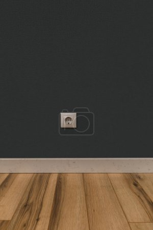 White power socket in wall over wooden floor