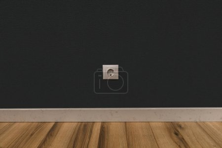 Photo for Single power socket in dark wall over wooden floor - Royalty Free Image