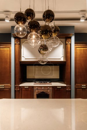 Stylish kitchen with elegant shiny table and chandelier
