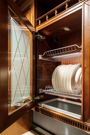 Stylish kitchen with white plates in cupboard