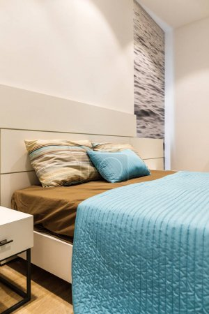Brown and blue bedclothes on bed in modern bedroom