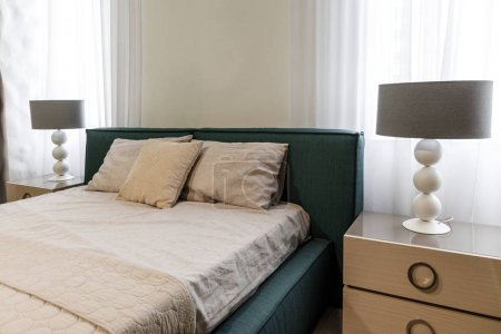 Large bed by window in modern bedroom