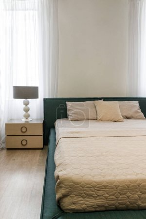 Photo pour Draps et couvertures légères sur le lit dans une chambre confortable - image libre de droit