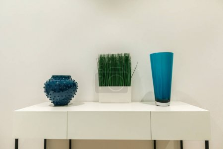 Blue vases and grass on white table by wall
