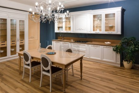 Photo for Table with chairs in stylish kitchen with chandelier - Royalty Free Image