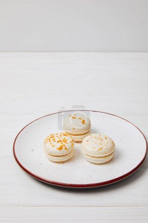 closeup shot of three macarons in plate on white wooden table