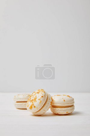 closeup view of three macarons on white wooden table