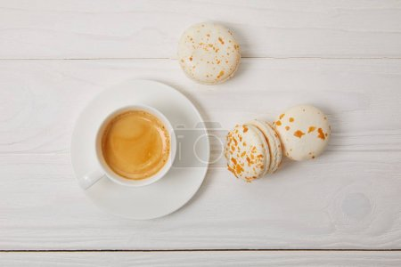 Photo for Top view of coffee cup and three macarons on white wooden table - Royalty Free Image