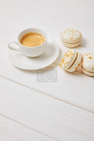 Photo for Coffee cup and three macarons on white wooden table - Royalty Free Image