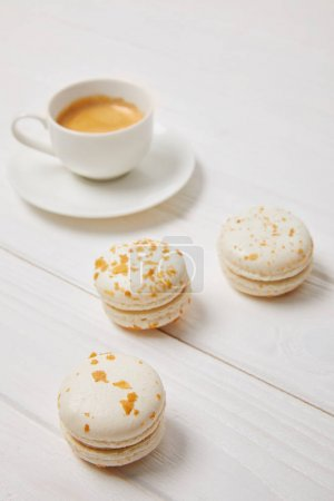 Photo for Closeup shot of coffee cup and three macarons on white wooden table - Royalty Free Image