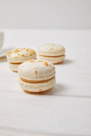 Photo for Partial view of coffee cup and three macaroons on white wooden table - Royalty Free Image