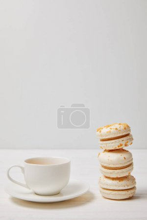 Photo for Closeup shot of coffee cup and stack of macarons on white wooden table - Royalty Free Image