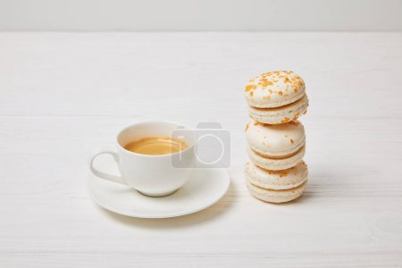 closeup shot of coffee cup and stack of macaroons on white wooden table