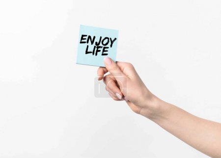 partial shot of woman holding blue sticky note with Enjoy life inspiration, isolated n white
