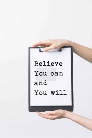 "partial view of woman holding clipboard with ""Believe You can and You will"" inspiration in hands, isolated on white"