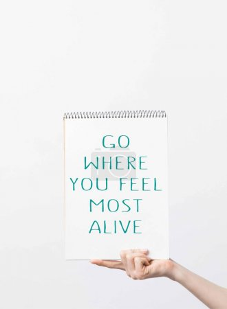 "partial view of woman holding sketchbook with ""Go where you feel most alive"" inspiration, isolated on white"