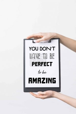 """partial view of woman holding clipboard with """"You dont have to be perfect to be Amazing"""" inspiration, isolated on white"""