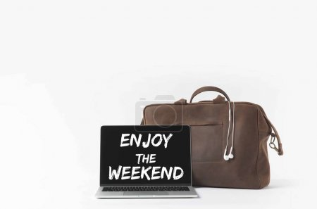 Photo for Laptop with Enjoy the weekend lettering on screen and stylish bag with earphones, isolated on white - Royalty Free Image