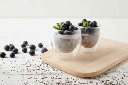close up view of chia puddings with fresh blueberries and mint on wooden cutting board on white tabletop