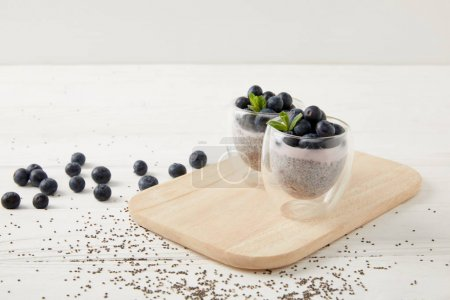 Photo for Close up view of chia puddings with fresh blueberries and mint on wooden cutting board on white surface - Royalty Free Image
