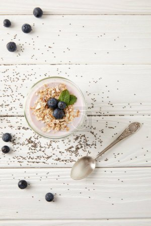 top view of spoon, chia pudding dessert with blueberries and oatmeal on white wooden surface