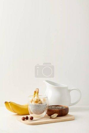 Foto de Cerrar vista de pudín de semilla de chia con trozos de plátano y avellanas en tabla de cortar madera con cuchara - Imagen libre de derechos