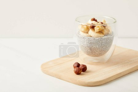 close up view of tasty chia seed pudding with pieces of banana and hazelnuts on wooden cutting board on tabletop