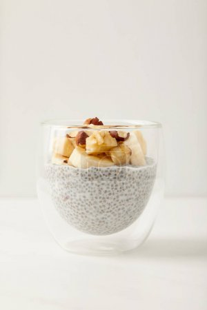 close up view of tasty chia seed pudding with pieces of banana and hazelnuts on white tabletop