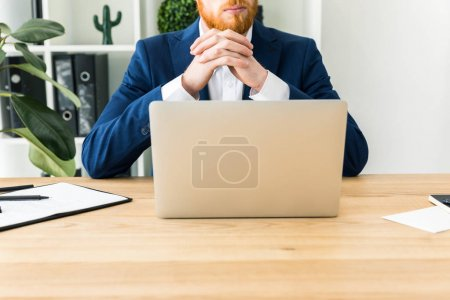 partial view of bearded businessman in suit sitting at workplace with laptop in office