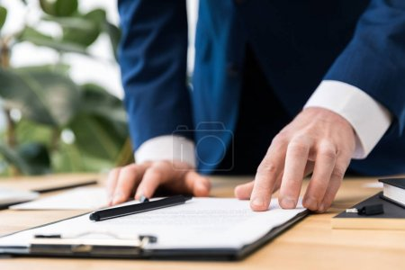 partial view of businessman at workplace with notepad in office