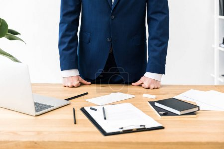 partial view of businessman at workplace with notebooks, notepad and laptop in office