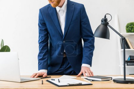 partial view of businessman at workplace with laptop, notebooks and notepad in office