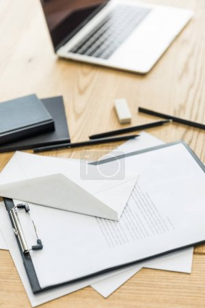 selective focus of notepad, notebooks and laptop on wooden tabletop
