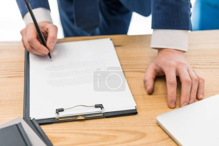 partial view of businessman signing papers at workplace