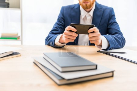 partial view of businessman in suit using smartphone at workplace with notebooks in office