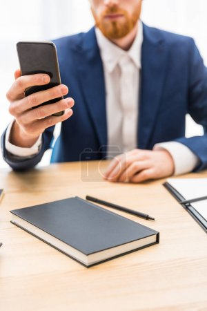 Photo for Partial view of businessman in suit using smartphone at workplace with notebook in office - Royalty Free Image