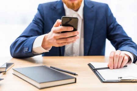 partial view of businessman in suit using smartphone at workplace with notebook in office