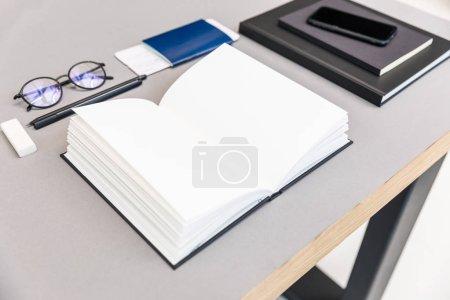 Photo pour Gros plan vue d'arrangement tas de vide portable ouvert, lunettes, passeport et billet au lieu de travail - image libre de droit
