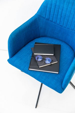 close up view of pile of black notebooks and eyeglasses on blue chair on white background