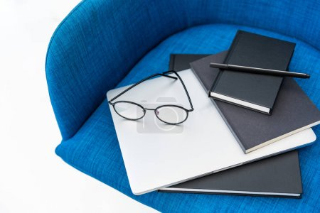 close up view of laptop, black notebooks and eyeglasses on blue chair isolated on white