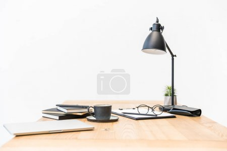 close up view of cup of coffee, eyeglasses, documents and laptop at workplace in office