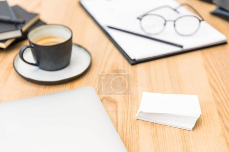 selective focus of cup of coffee, eyeglasses, documents and blank cards at workplace in office