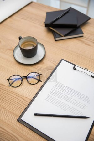 close up view of cup of coffee, eyeglasses, documents on wooden tabletop