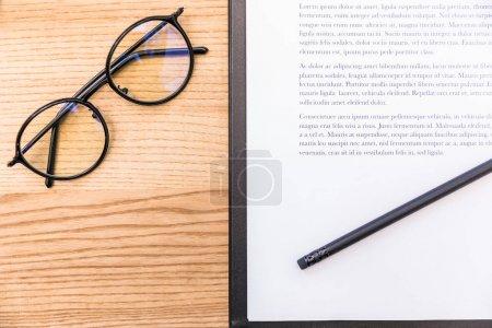 Photo pour Vue de dessus des lunettes, crayons et bloc-notes avec des documents sur la surface en bois - image libre de droit