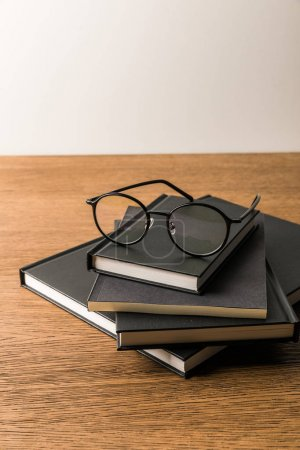 Photo for Close up view of pile of black notebooks and eyeglasses on wooden tabletop - Royalty Free Image
