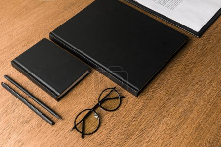 close up view of black notebooks, eyeglasses and stationery on wooden tabletop