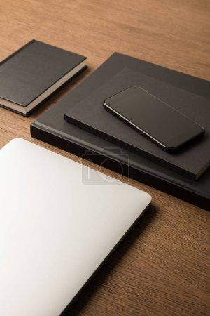 cerrar vista de portátil, pila de negro notebooks y smartphones en tablero de madera