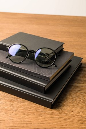 close up view of pile of black notebooks and eyeglasses on wooden tabletop