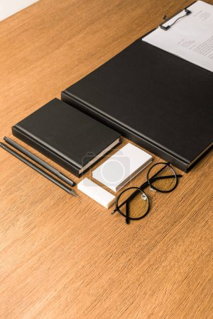 close up view of black notebooks, eyeglasses and blank card at workplace