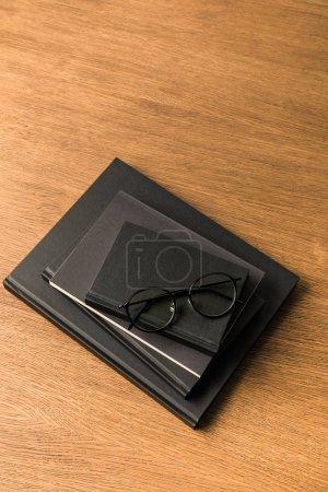 vista superior de la pila de cuadernos negros y anteojos en tablero de madera